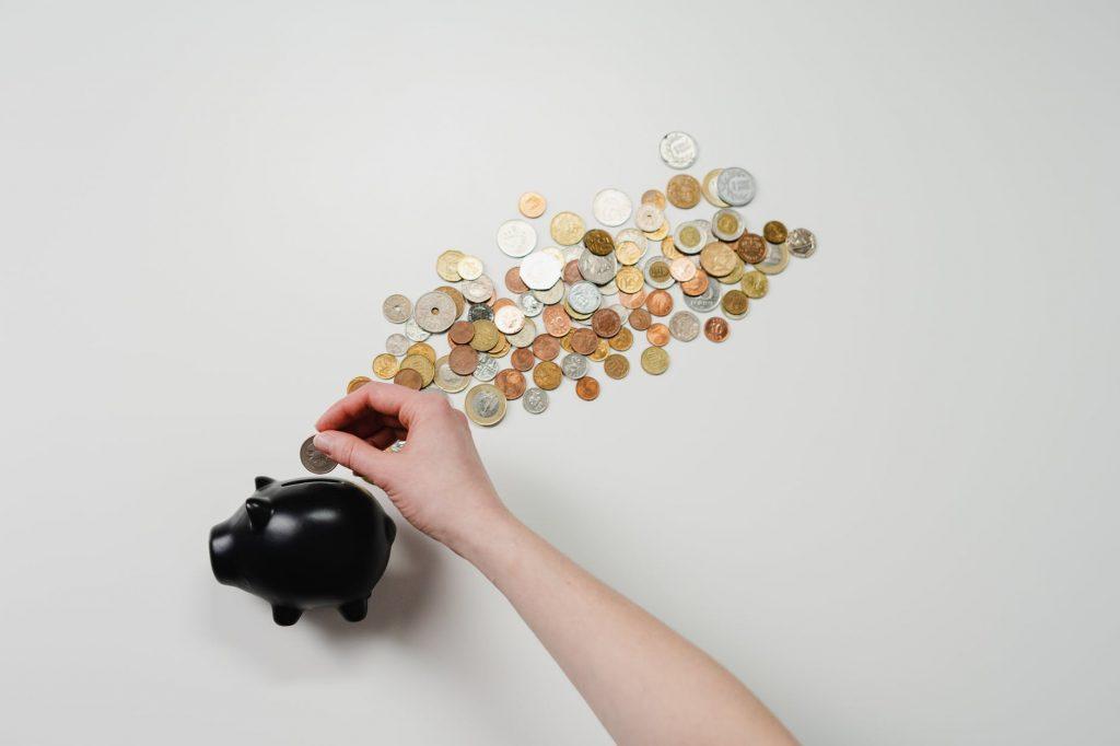 Foto de uma pessoa economizando e juntando moedas
